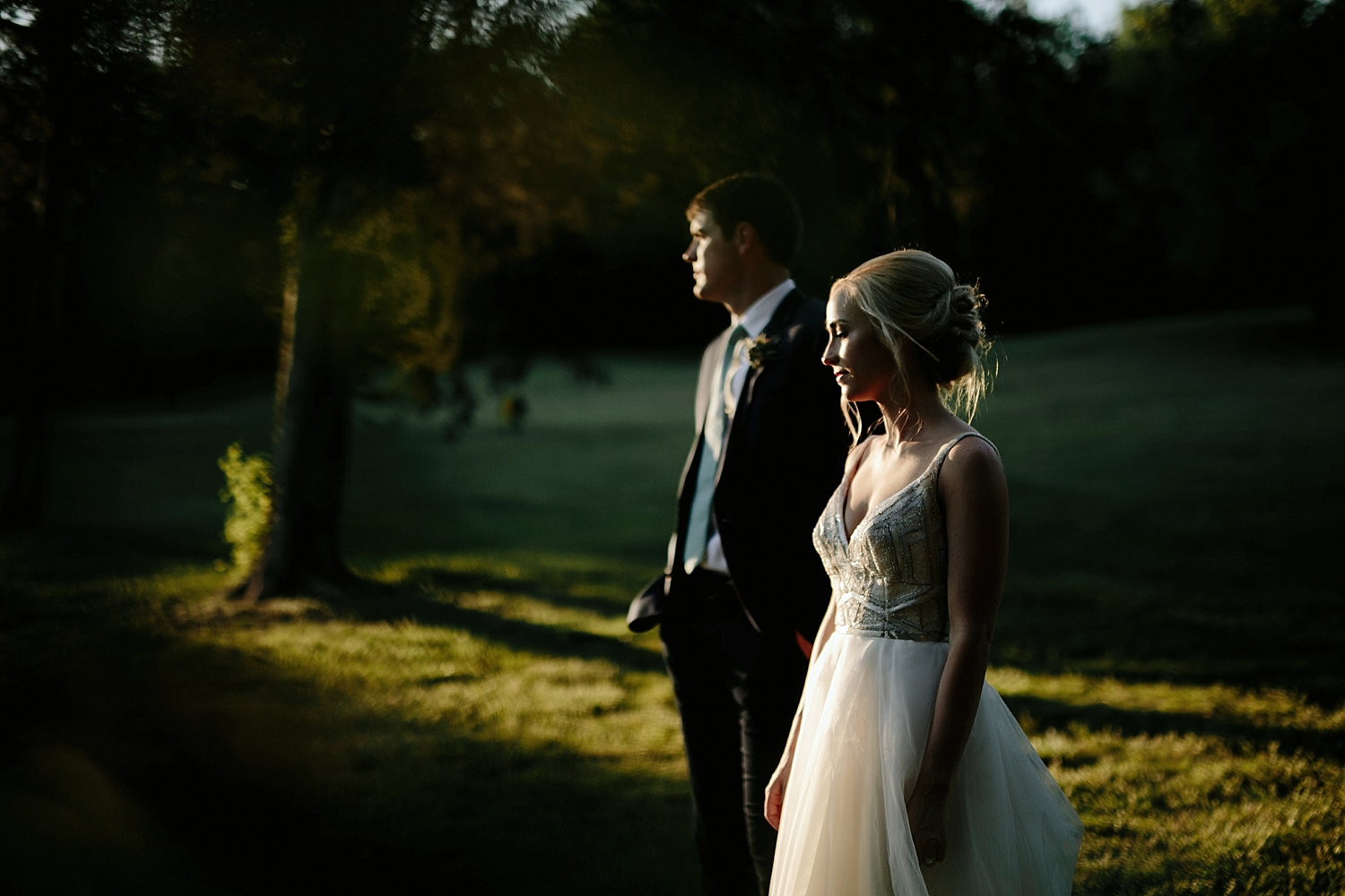 bride and groom standing in the suns rays