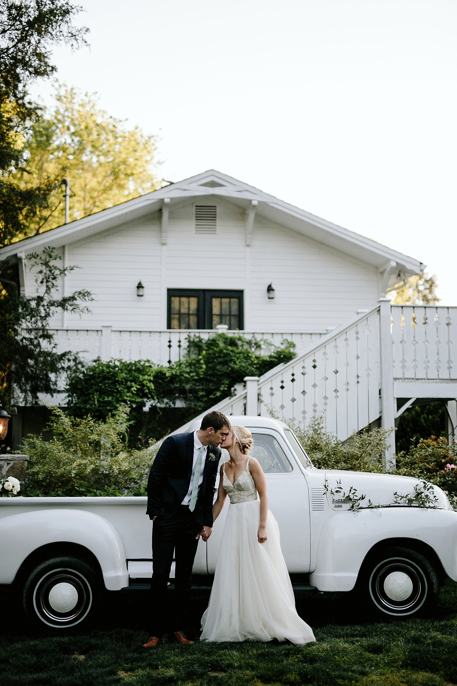 bride and groom kissing in front of antique truck