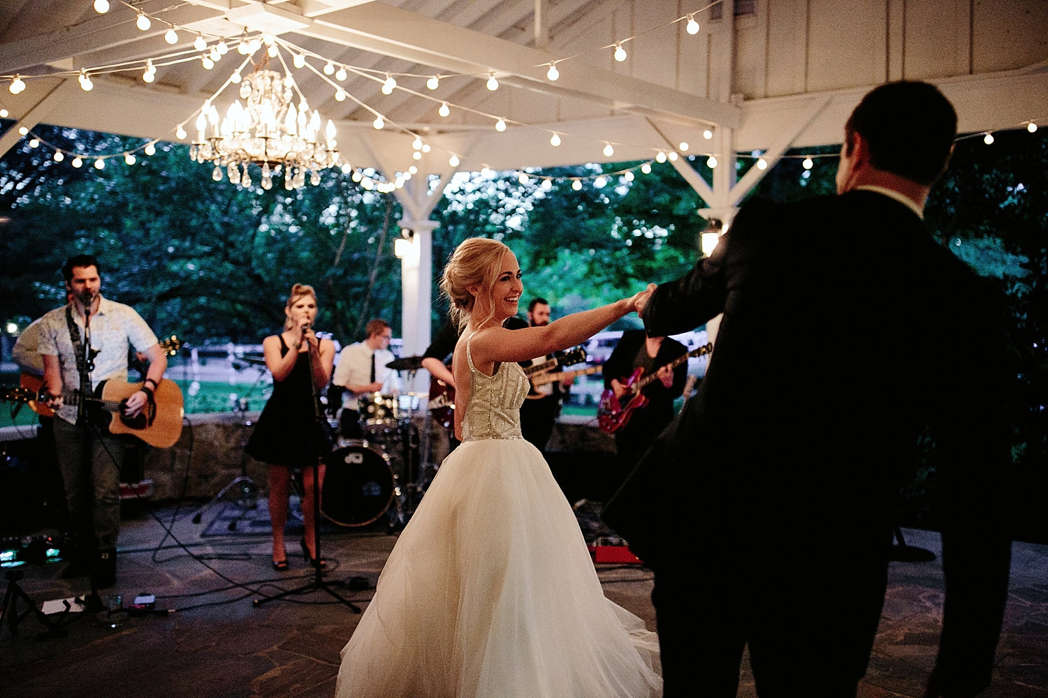 bride and groom dancing with musicians in the background