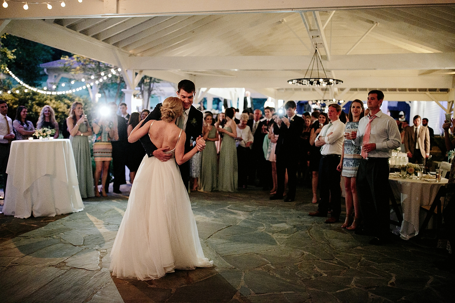bride and groom dancing while guests watch