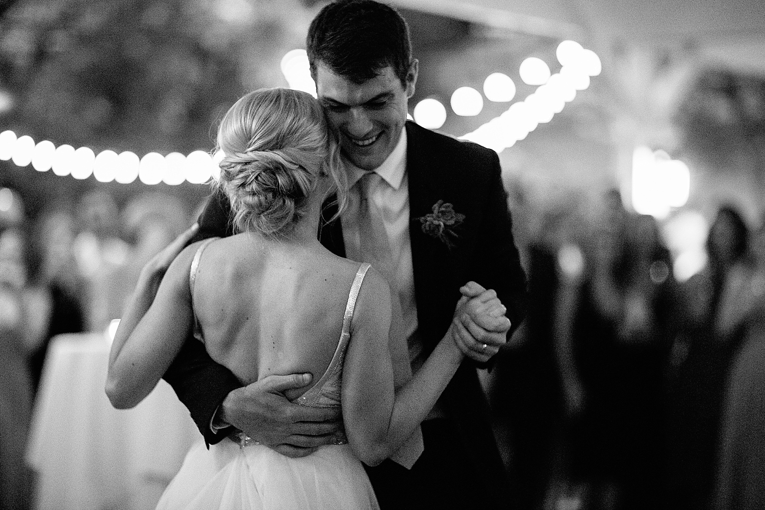 groom holding bride close during first dance
