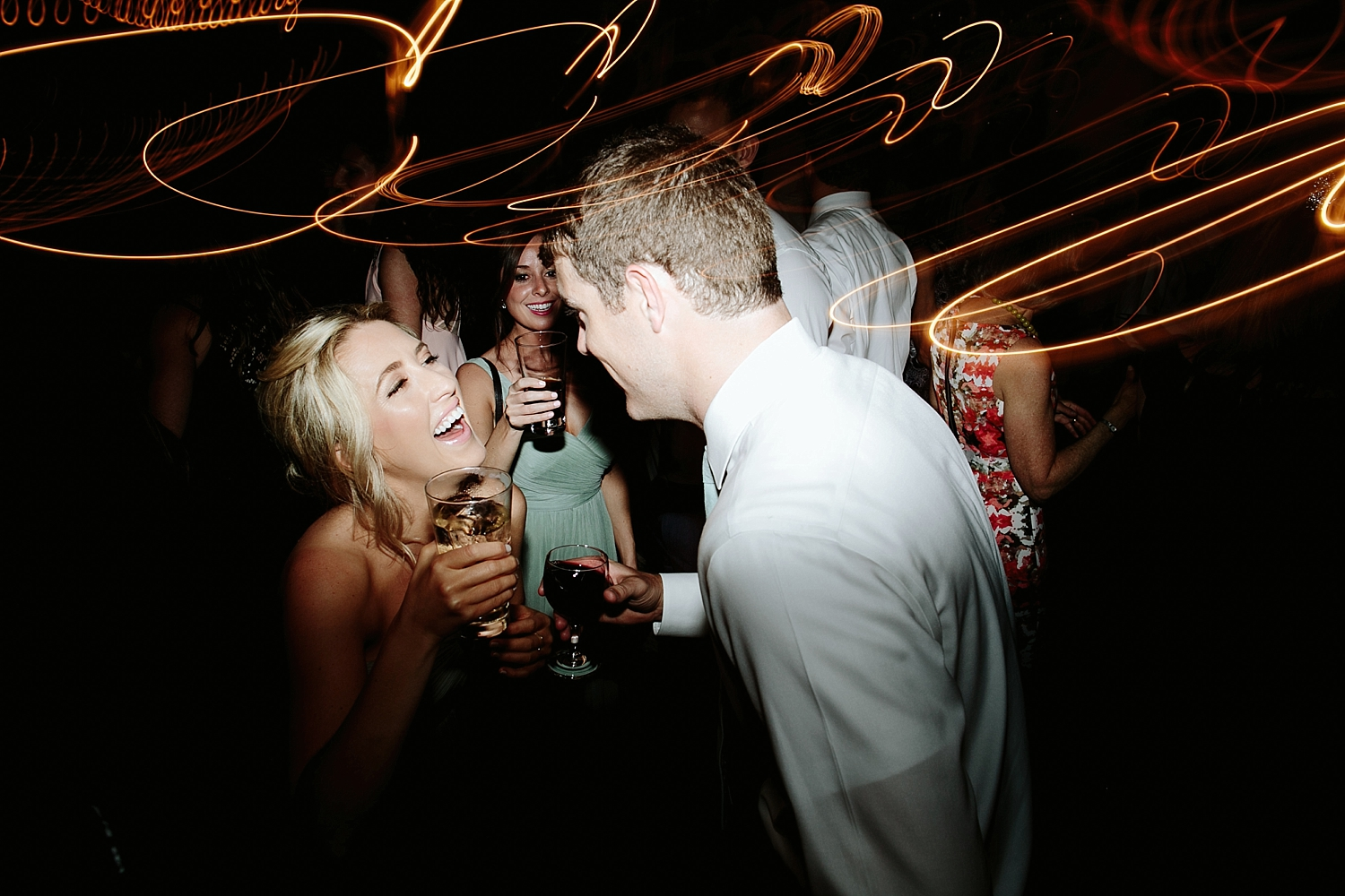 bridal party dancing with drinks in hand