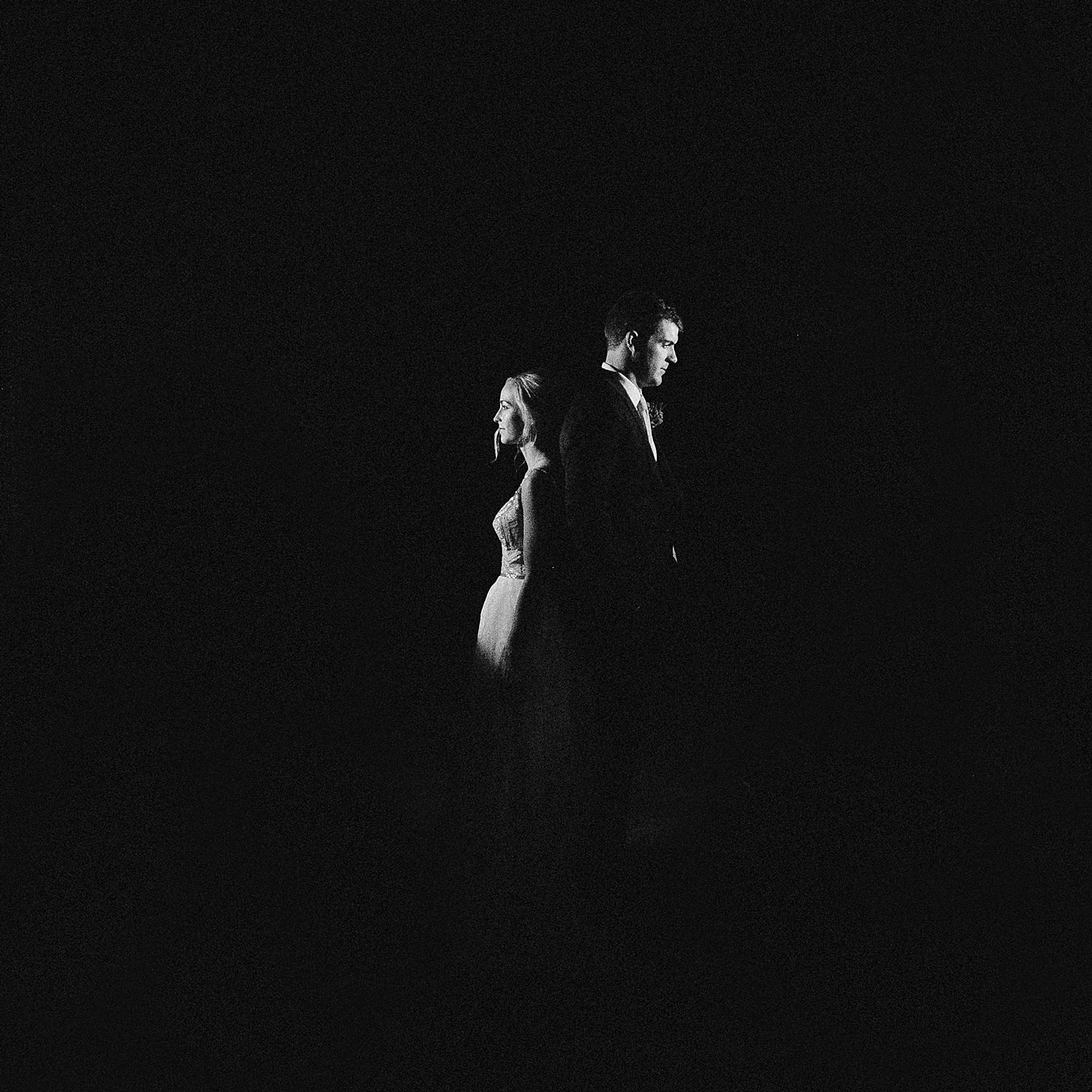 bride and groom standing back to back at night