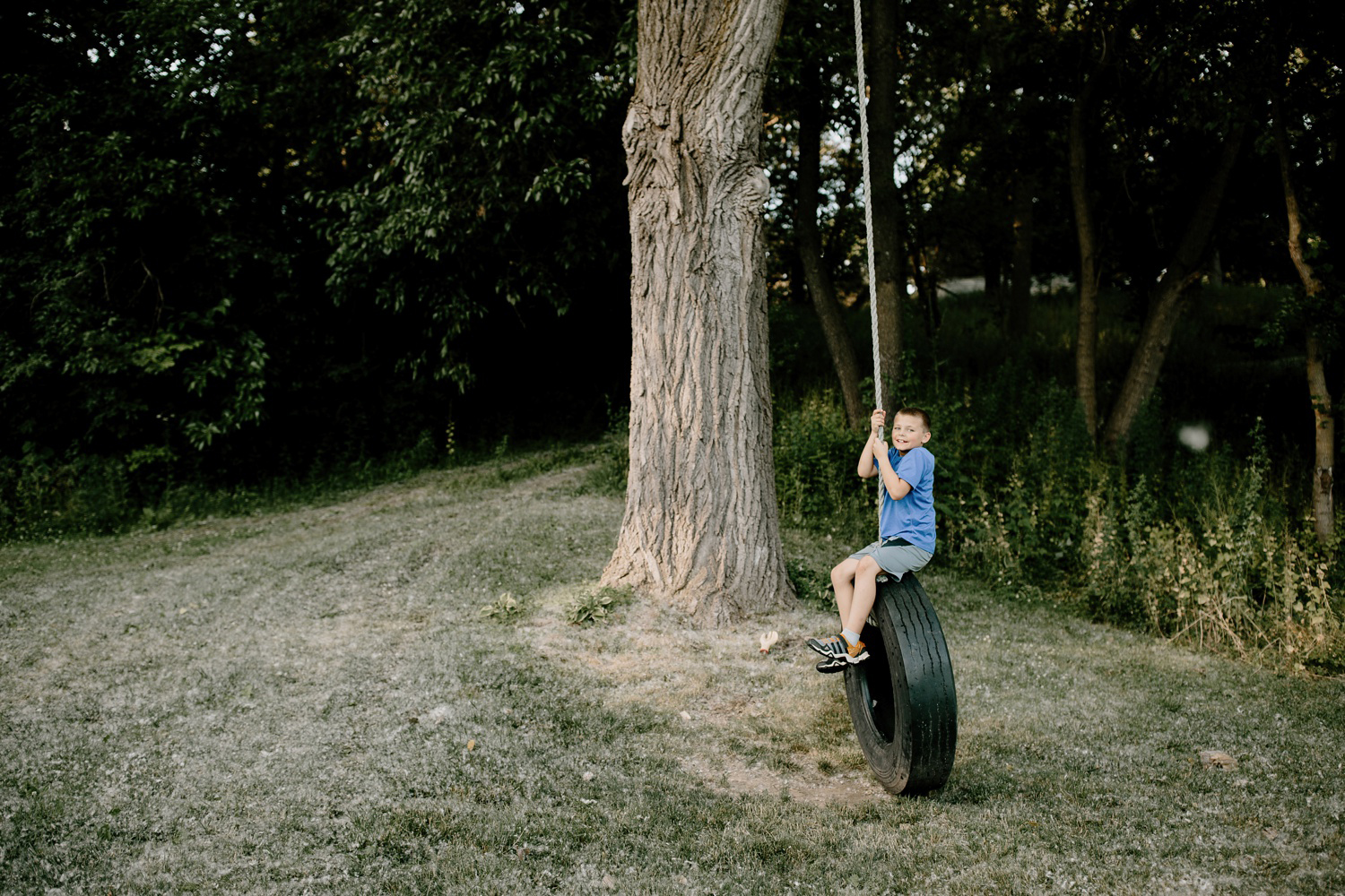 boy swinging on tire swing