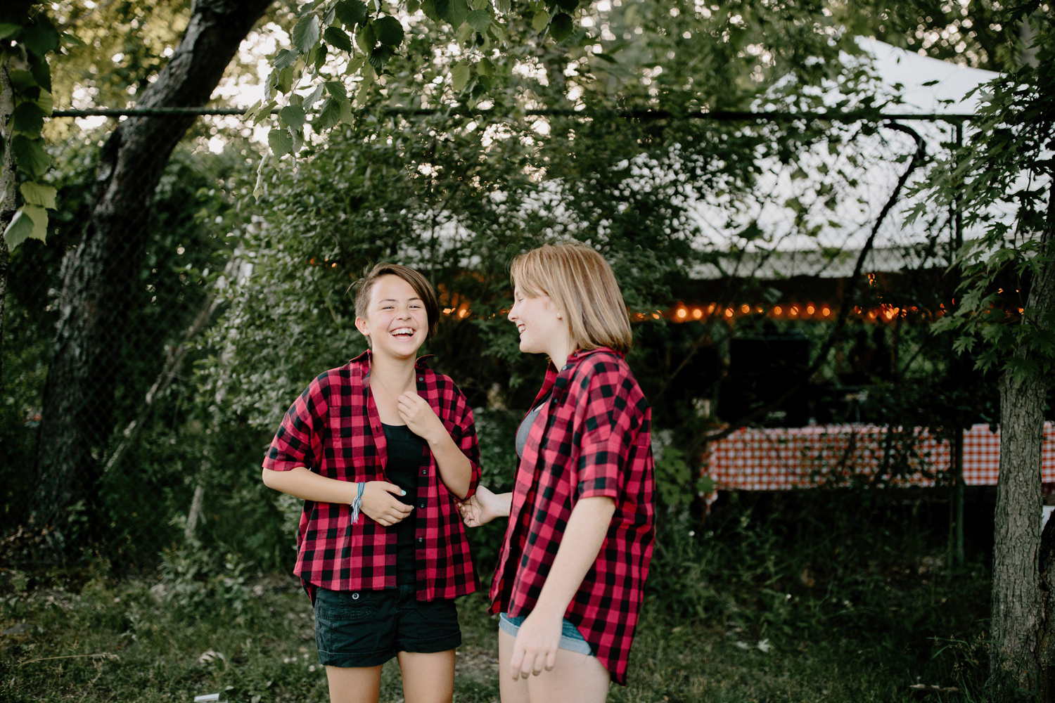girls laughing in matching plaid shirts