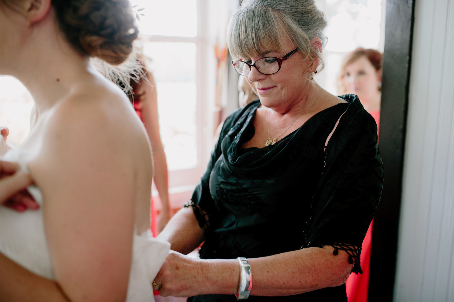 mother of the bride zipping up dress