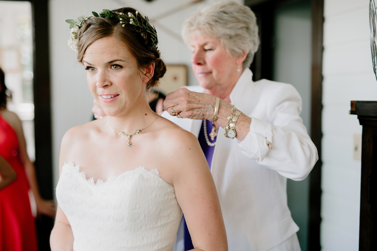 friend of the bride putting on necklace