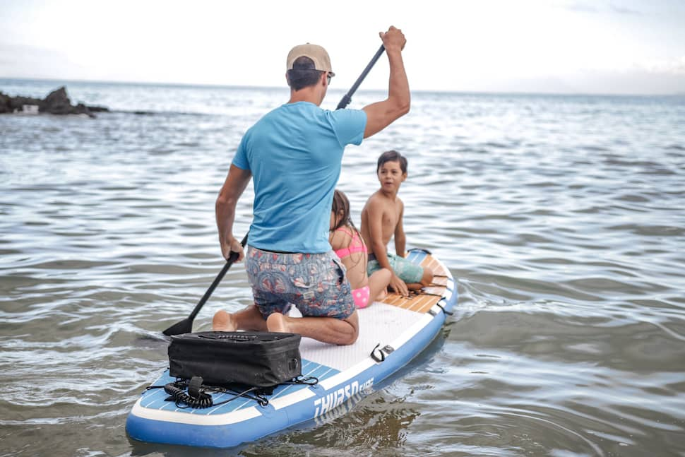man knee paddles a Thurso Surf Multipurpose sup with kids