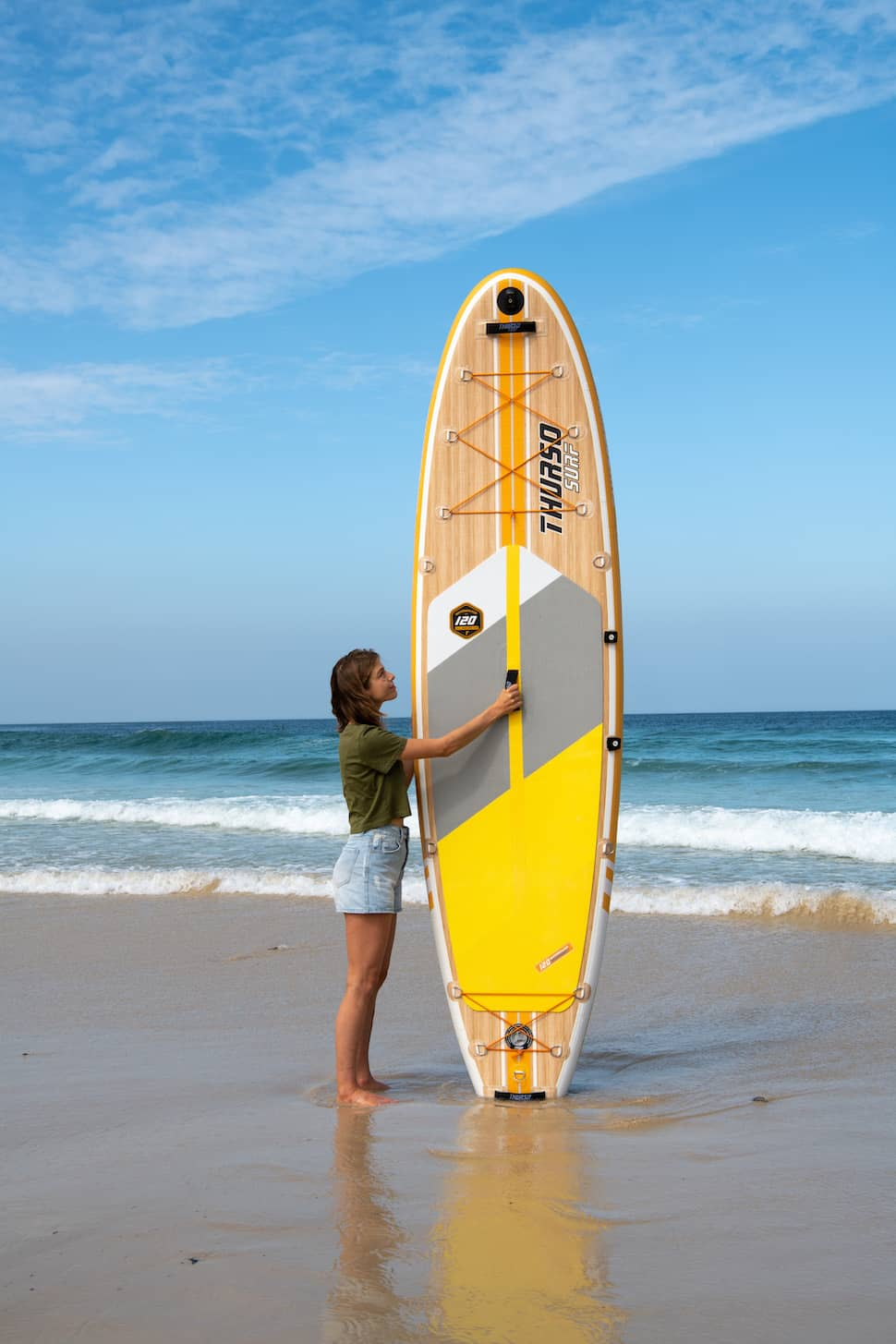 woman stands next to Thurso Surf Waterwalker All-around SUP on beach in front of breaking waves