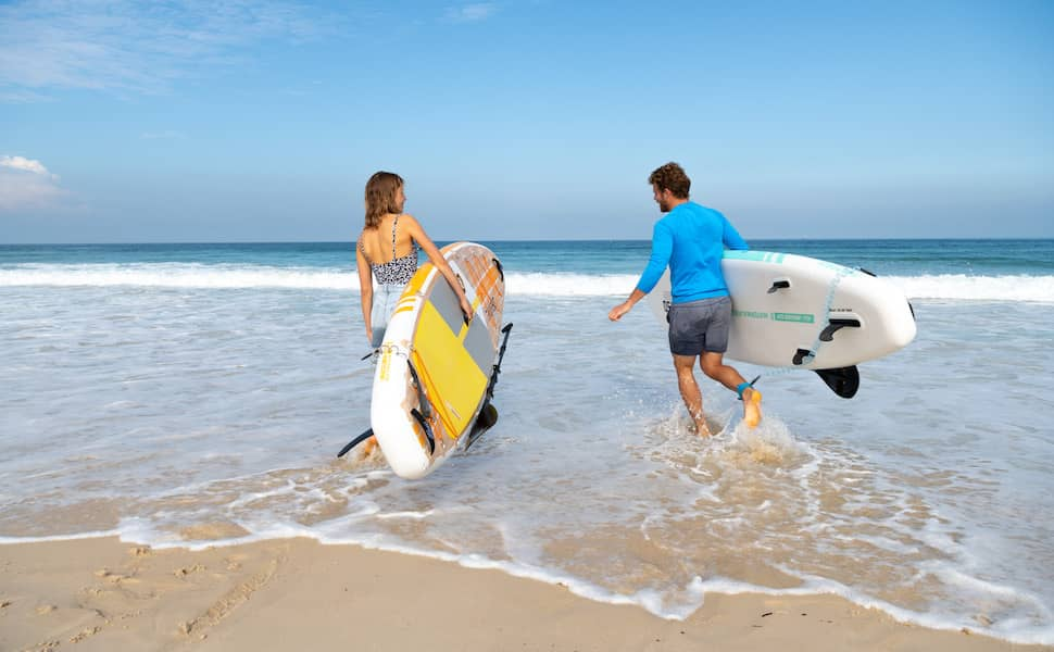 man and woman discuss the differences between all-around vs multipurpose SUP while carrying iSUPs into the water