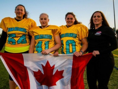 Left to right: Capital Area Lady Gladiators members Robyn Neill, Kris Chatterton, Alex Black and Cheryl O'Leary proudly display the Canadian flag. Photo credit: Baxter Photography