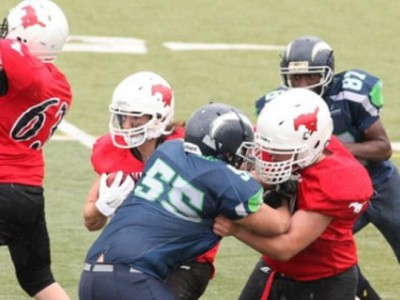 Matt Krzysztalowicz (in the red) blocks a defender and opens a whole for his running back.