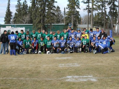 two teams after a hard fought game getting together for a multi team picture- Carrot River Wildcats in green and Cumberland House Islanders in blue.