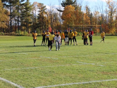 Coach Jean in the yellow demonstrating to his recieiving core how to burn a defender