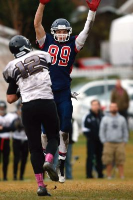 Josh Hyer (#99) jumps into the air. By Keith Johnston.