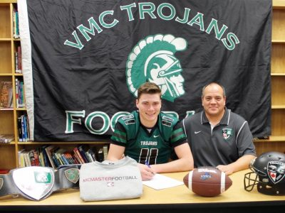 Andre Dueck signs his LOI with McMaster. Courtesy of Vincent Massey Collegiate Twitter account.