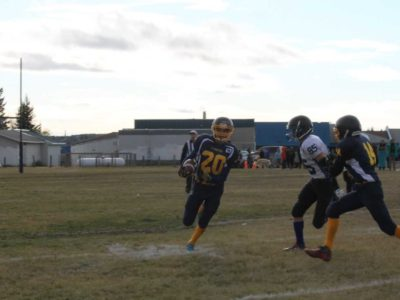 Sandy Bay player no. 20 Cory Spencer , pursued by Cumberland no. 85 Rustin Deschambeault and assisted  by Sandy bay no.14 Cornelius Whitebear