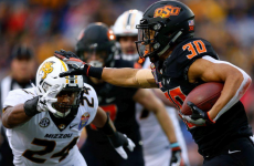 MEMPHIS, TENNESSEE - DECEMBER 31: Chuba Hubbard #30 of the Oklahoma State Cowboys runs with the ball as Terez Hall #24 of the Missouri Tigers defends during the first half of the AutoZone Liberty Bowl at Liberty Bowl Memorial Stadium on December 31, 2018 in Memphis, Tennessee.Jonathan Bachman / Getty Images