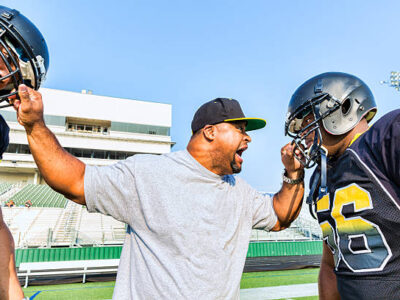 A coach yells at his players for not running the correct play during a scrimmage game.