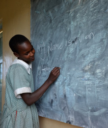 Masai Mara,Kenya,Africa; October 17.2011 : unidentified student writes his name on the blackboard at school in Masai Mara