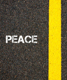 Antonym concept of PEACE versus WAR written over tarmac road marking yellow paint separating line between words