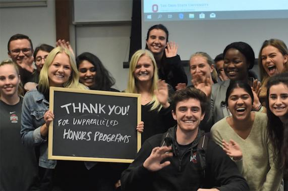 """Honors Cohort students hold up a """"Thank you for unparalleled honors programs"""" sign."""