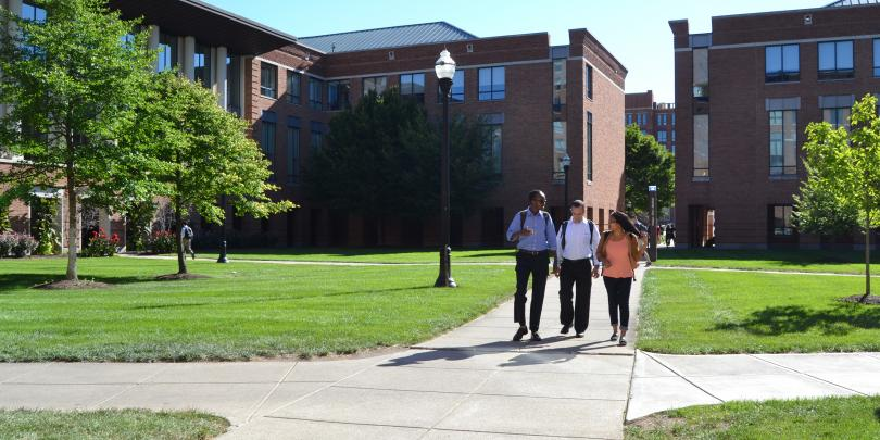 Three students walking in the Alutto Quad on Fisher's campus