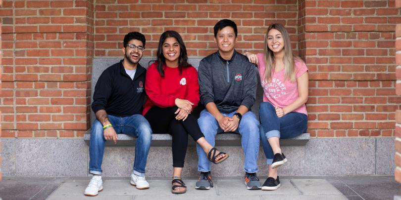 Four Fisher students sitting on bench together