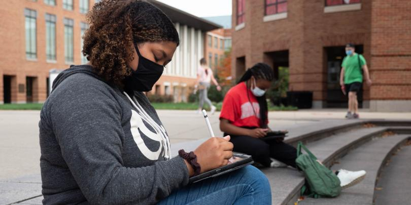 Students sitting in front of Fisher Hall wearing masks