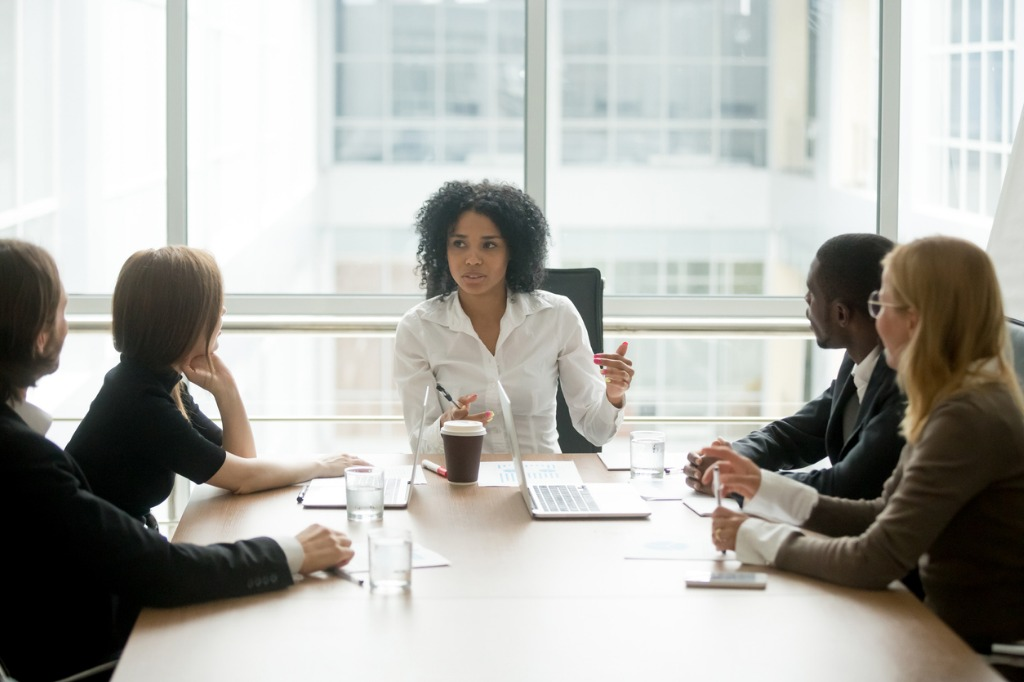 Woman talking to people in a meeting.