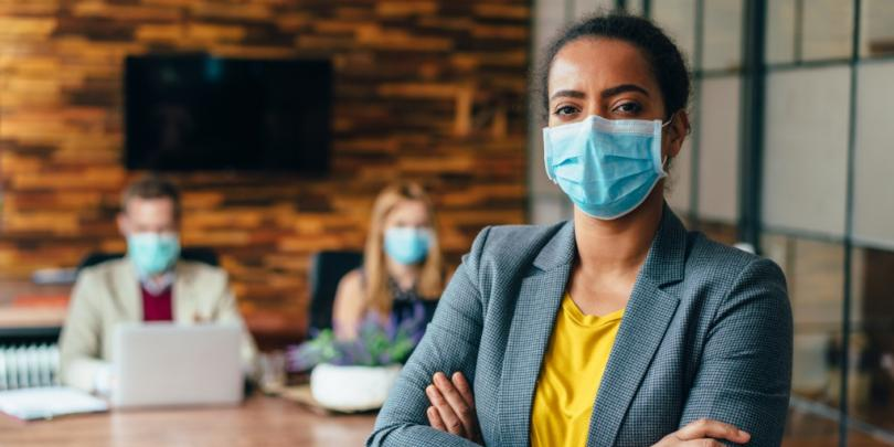 Business-people working with face masks in office