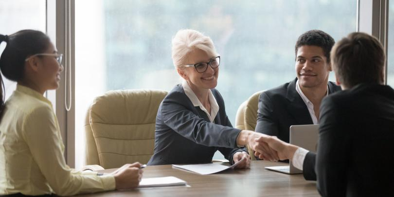 Female executive greeting someone at a table