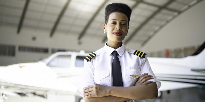 African-American female pilot standing in front of a plane