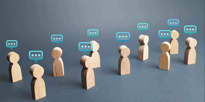little wooden figures with what appears to be speech bubbles above their heads (no words in bubbles, just dots)