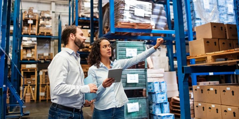 A man and a woman inspecting a warehouse