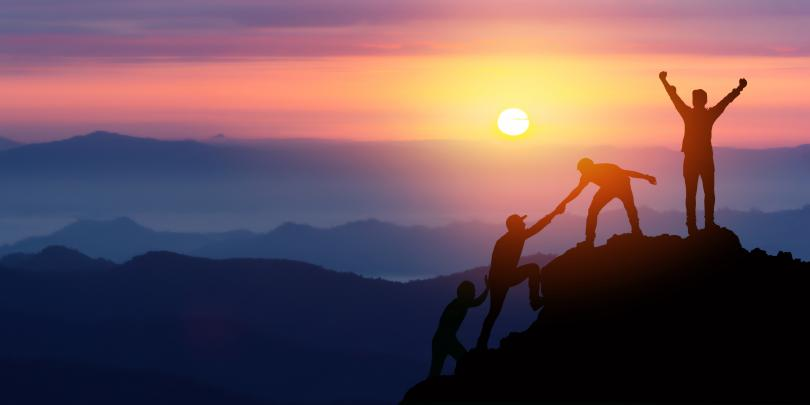 People helping each other up a mountain