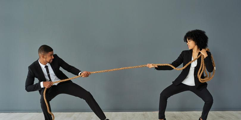 A man and a woman in business clothes playing tug of war