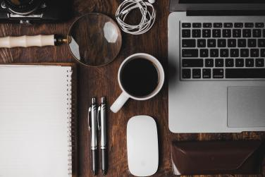 picture of laptop, coffee, pens and notebook