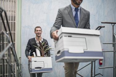 People carrying boxes out of an office
