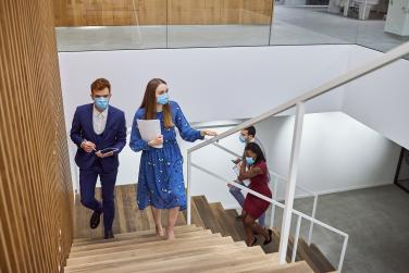 People in masks walking up office stairs