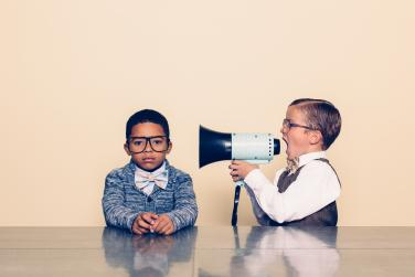 Young boy with megaphone tries to get another young boy to listen