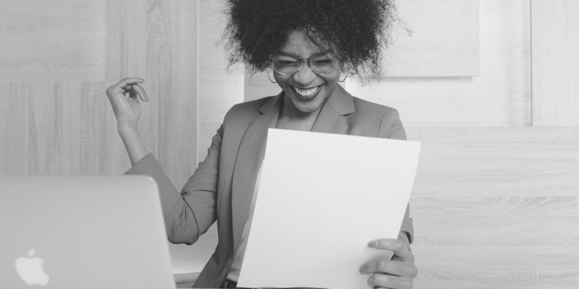 Black and white image of a woman sitting at her computer looking at papers, text overlay in red text box: 5 key domains for profitable growth