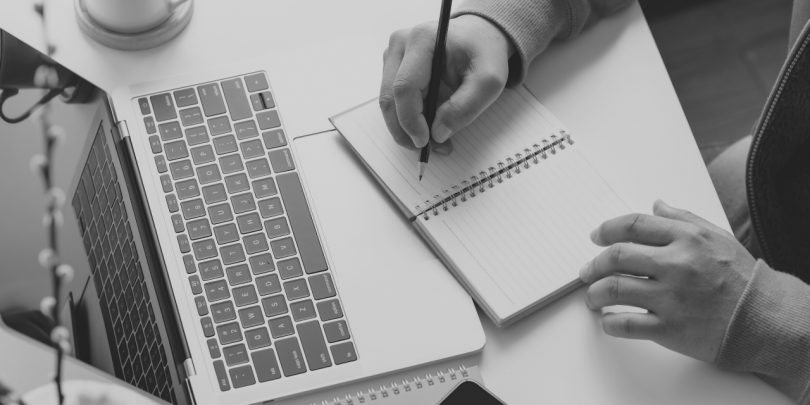 Black and white image of someone taking notes in a notebook next to their open laptop
