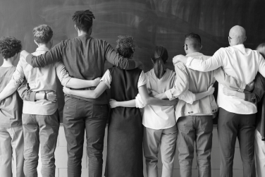Diverse group stand arm in arm with their backs facing the camera