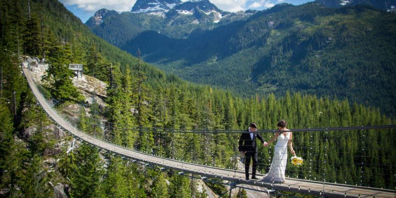 Josh Meyer in tuxedo, walks with his wife, in wedding dress across a suspension bridge in the mountains on their wedding day