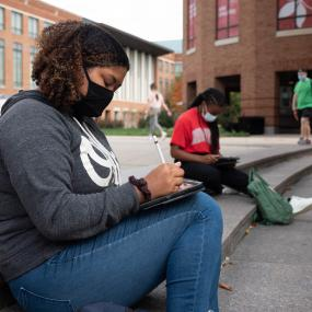 Two students sitting on Fisher Hall steps wearing masks.