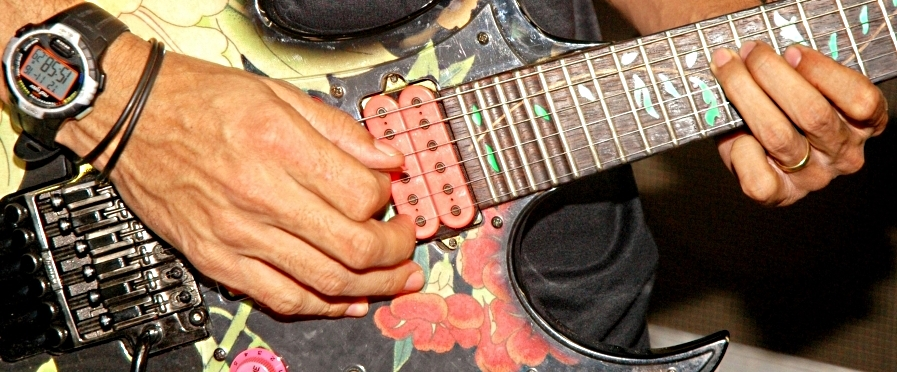 photo of man improvising on his guitar