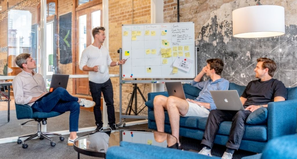 Entrepreneur presenting branded domains to team with whiteboard