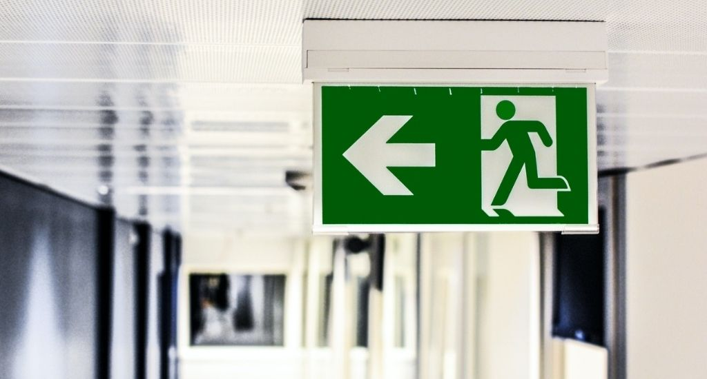 Green emergency evacuation sign pointing to exit