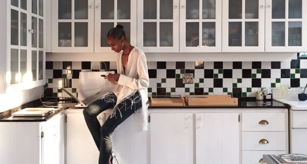 Interior design entrepreneur sitting on kitchen counter